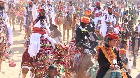 senhor : JAISALMER, INDIA - FEBRUARY 08, 2017: Camel and indian men wearing traditional Rajasthani dress. Desert contest as part of the Desert Festival in Jaisalmer, Rajasthan, India