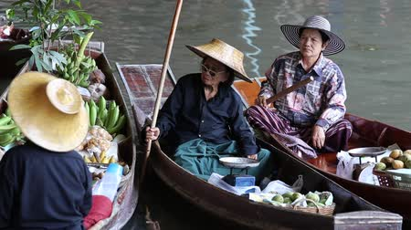 ratchaburi : RATCHABURI, THAILAND - APRIL 27, 2014: Unidentified people on food boats at Damnoen Saduak floating market. Damnoen Saduak is a very popular tourist attraction near Bangkok in Thailand.