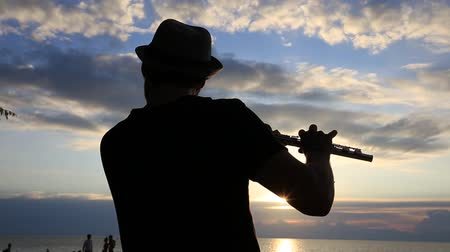 flutist : KOH PHANGAN, THAILAND - JANUARY 14, 2017: An unidentified man playing the flute at sunset on the beach during a full moon party in island Koh Phangan, Thailand