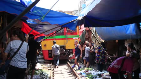 samut : MAEKLONG, THAILAND - MARCH 21, 2018: Mae Klong Railway Market, Hoop Rom Market, in Samut Songkhram Province, commonly referred to as Siang Tai, life-risking, train local market near Bangkok, Thailand