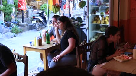 full moon : KOH PHANGAN, THAILAND - MARCH 01, 2018: Unknown people sitting in a beach cafe eating fast food before the Full Moon Party on the island of Koh Phangan, Thailand Stock Footage