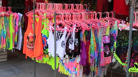 consumir : KOH PHANGAN, THAILAND - MARCH 02, 2018: Colorful t-shirts are put up for sale on the beach before the Full Moon Party on the island of Koh Phangan, Thailand Stock Footage