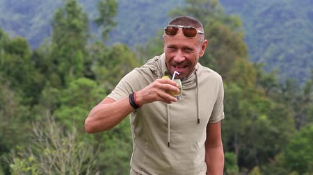 não barbeado : Portrait of a happy man who drinks a cocktail on a nature background, Bali, Indonesia. People and lifestyle concept. Adult man portrait close up Vídeos