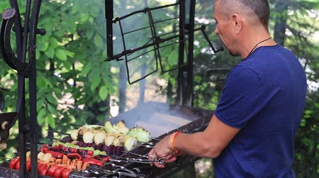domates : Middle-aged man is preparing shish kebabs from vegetables on a grill in nature, close up. The concept of a healthy lifestyle. Stok Video