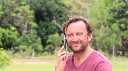 não barbeado : Unshaven middle-aged man with glasses talking on cellphone on the nature in summer day, close up