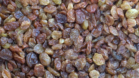 uva passa : Pile raisins background, close up rotation, top view. Macro dry raisins