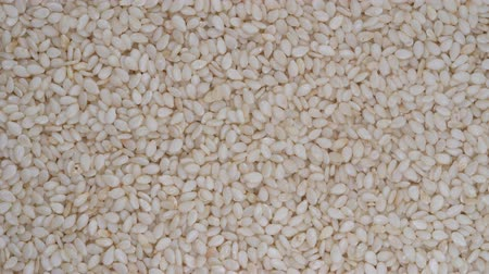 kabuksuz tahıl : Pile sesame seeds background, close up rotation, top view. Macro sesame seeds