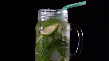цитрусовые : Lemon fruit Caipirinha alcoholic beverage of a glass in a glass mug on a black background, close up. Rotates cold drink with green mint leaf, lime and ice, macro