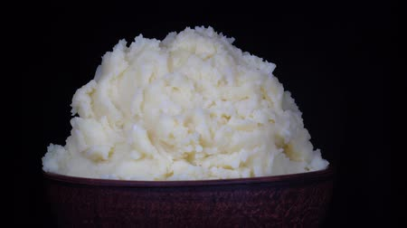 пюре : Ukrainian national food is mashed potatoes in plate, close up. Rotates bowl with mashed potatoes in black background, macro