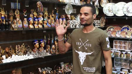 statuette : SHARM EL-SHEIKH, EGYPT - MAY 21, 2018: Egyptian man sells souvenirs for tourists in its store at Soho square in Sharm El Sheikh, South Sinai, Egypt