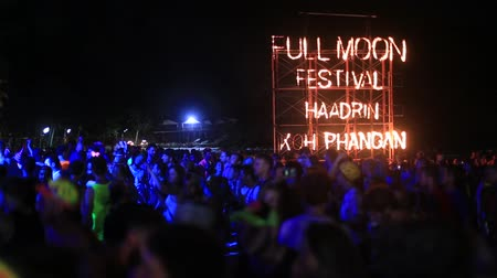 signboard : KOH PHANGAN, THAILAND - MARCH 02, 2018: Girls and guys participate in the Full Moon party in island Koh Phangan, Thailand. Full Moon Party fire sign on Haad Rin beach