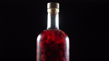 şişeler : Rustic glass bottle of sweet cherry liqueur on black background, close up. Rotates cold cherry brandy drink with red cherries, macro