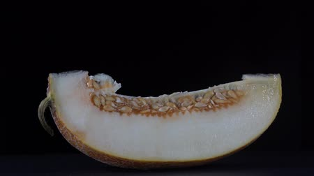 мускусная дыня : Yellow melon on a black background, close up. Rotates slice yellow melon, macro Стоковые видеозаписи