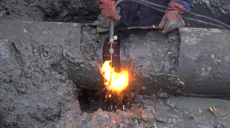 welding torch : Worker welder eliminate the city in Kiev, Ukraine. Worker using a metal pipe during a water pipeline accident Stock Footage