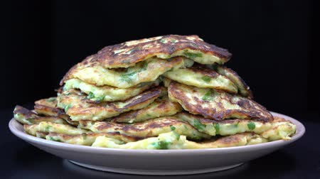 baked pumpkin : Vegetable pancakes from zucchini on black background, close up, rotates. Traditional Ukrainian cuisine