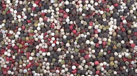 peppercorn : Black, white and red dry pepper background, rotation. Front of the camera rotates the plate with black, white and red pepper, close up, top view, macro peppercorns Stock Footage