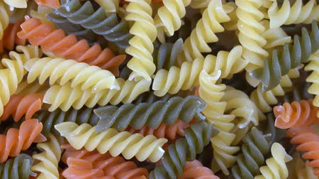 üç renkli : Multicolored pasta background, rotating, top view. Rotation of colored spiral pasta. Heap of uncooked pasta. Italian food close up. Delicious italian fusilli, tricolor pasta, food background