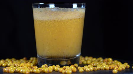 sea buckthorn : Fresh organic sea buckthorn smoothie in glass on black background, close up. Rotates cold drink with orange yellow common sea buckthorn berries, macro Stock Footage