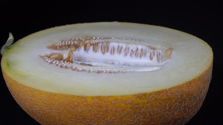 мускусная дыня : Yellow melon on a black background, close up. Rotates half yellow melon, macro Стоковые видеозаписи