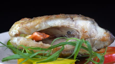 senki : Fried fish served on a black background. Fried piece of carp with vegetables. Close up