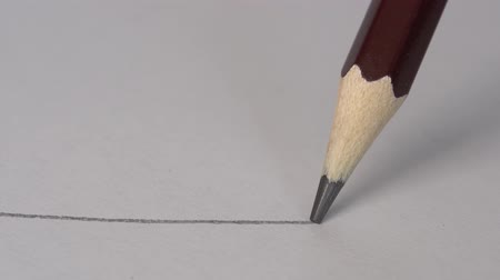 exercício : Graphic wooden pencil on white paper. Close up, macro, 4k