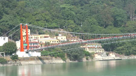 RISHIKESH, INDIA - NOVEMBER 08, 2018: Unidentified people crossing Laxman Jhula footbridge on the river, Ganges, India