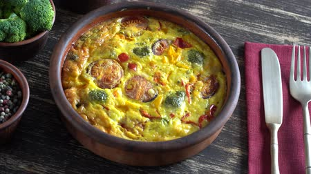 ceramika : Ceramic bowl with vegetable frittata, simple vegetarian food. Frittata with egg, tomato, pepper, onion, broccoli and cheese on wooden table, close up. Italian egg omelette, rotates