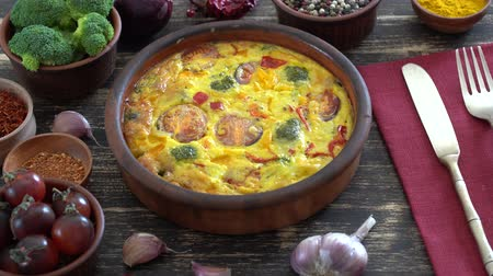 Ceramic bowl with vegetable frittata, simple vegetarian food. Frittata with egg, tomato, pepper, onion, broccoli and cheese on wooden table, close up. Italian egg omelette, rotates