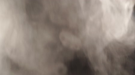 White smoke on black background in slow motion. White steam spins and rises