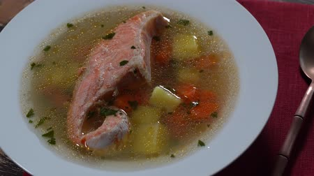 parsley : Fresh salmon fish soup with carrots, potatoes and herbs in a white plate, close up, rotates. Tasty dinner consists of a fish soup with salmon Stock Footage