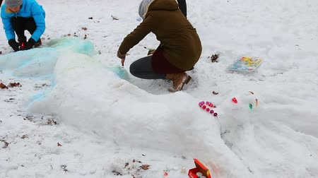 kardan adam : Moscow, Sokolniki Park-January 27, 2018: Teens playing in winter Park and make a snow sculpture