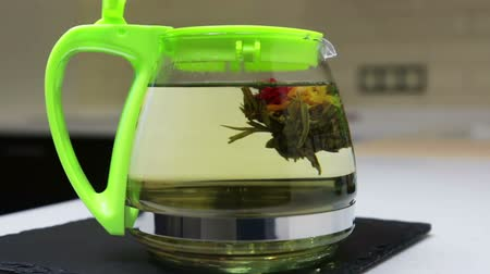 brew tea : brewing flower tea in the kitchen in a glass teapot. Time lapse