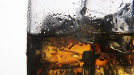 alkoholos : whiskey in a glass with ice on a light background in the contour light. Alcoholic beverages. video rotation