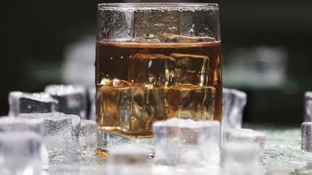 виски : whiskey in a glass with ice on a light background in the contour light. Alcoholic beverages. video rotation