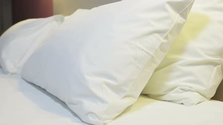 матрац : Pillows on a large king-size bed. Concept on preparation of the bed in a hotel room or at home. dolly video Стоковые видеозаписи