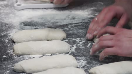 chefs table : cook kneads the dough and gives it a shape before baking Stock Footage