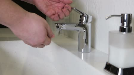lavatório : person washes his hands under water faucet in a luxurious hotel room or at home in the bathroom.