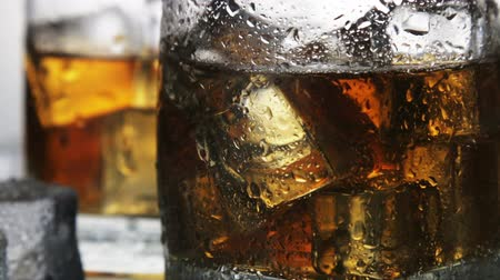 pohárek : whiskey in a glass with ice on a light background in the contour light. Alcoholic beverages. video rotation