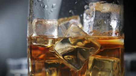 pohárek : whiskey in a glass of ice on a black background. Alcoholic beverages. video rotation
