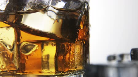 выстрел : whiskey in a glass with ice on a light background in the contour light. Alcoholic beverages. video rotation