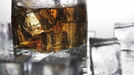pohárek : whiskey in a glass with ice on a light background in the contour light. Alcoholic beverages. video dolly