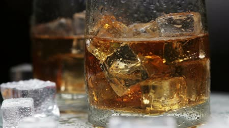 nightcap : whiskey in a glass of ice on a black background. Alcoholic beverages. video dolly Stock Footage