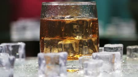 nightcap : whiskey in a glass of ice on a black background. Alcoholic beverages. video rotation
