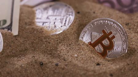 soluções : Bitcoin BTC the new virtual Internet cryptocurrency, banknotes of dollars buried in the sand. Slider video