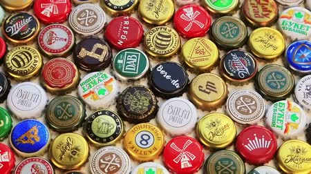 aluminium : Moscow, Russia-30, 2018: beer bottle caps background, mix of different world brands: grolsch, Bud, Bavaria, Miller, Heineken, Baltika; Corona Extra, etc. Rotation video