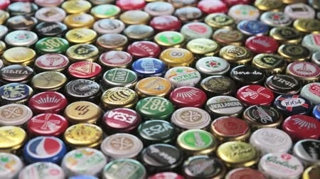 reciclado : Moscow, Russia-September 7, 2018: metal caps from different drinks, from beer, soda, cola, mineral water. Popular brands: Coca Cola, Fanta, Gesser, grolsh, Heineken etc. Dolly video Stock Footage