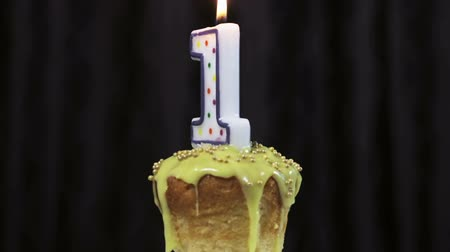 カップケーキ : cupcake with a burning candle with the number 1. Congratulations on your first birthday. video rotation