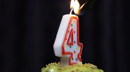 cupcake with a burning candle with the number 4. Congratulations on your first birthday. video rotation