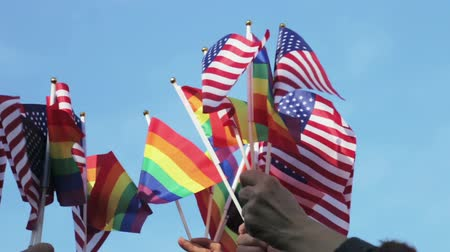flags of the us and the LGBT community in hands on the background of blue sky