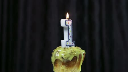 cupcake with a burning candle with the number 1. Congratulations on your first birthday. video rotation